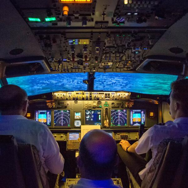 Three men in 737 800 flight simulator