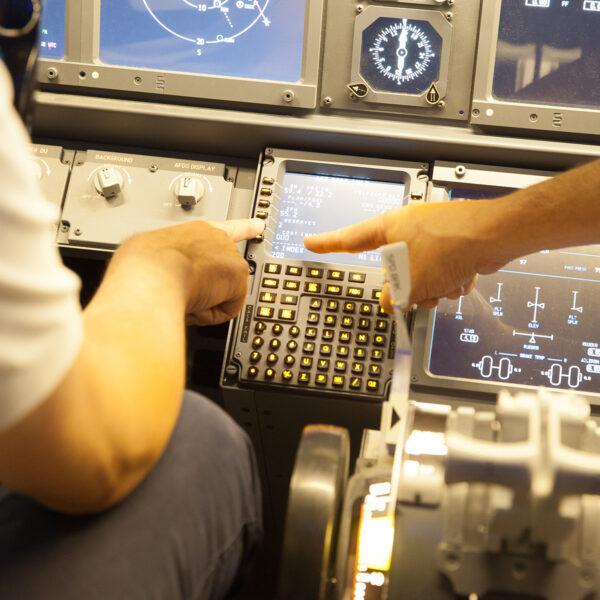 Pilot points to equipment 737 800 simulator