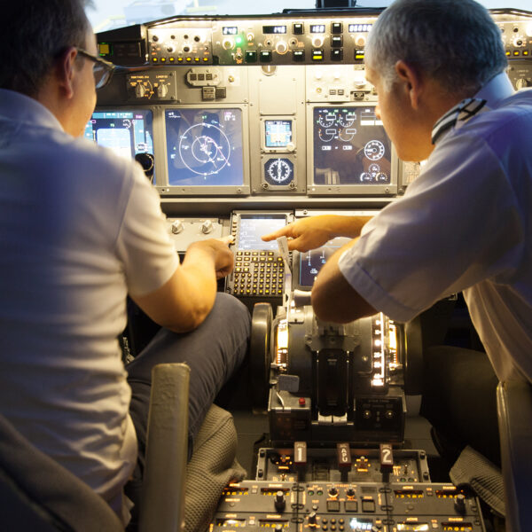 Man points out to student in 737 800 cockpit