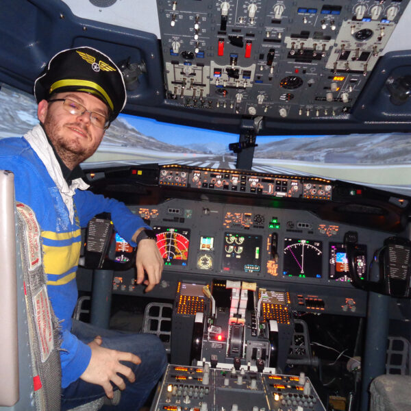 Man poses in captains hat, 737 800 simulator