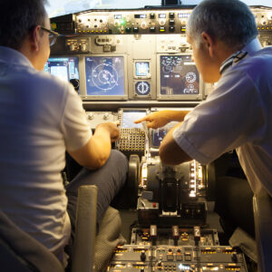 Pilot points out something to student in 737 800 simulator
