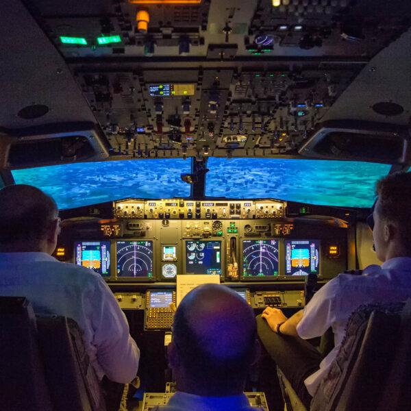 Three men in fixed base 737 800 simulator
