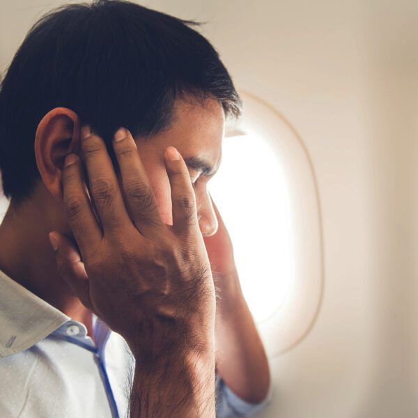 Man hold his head due to fear of flying
