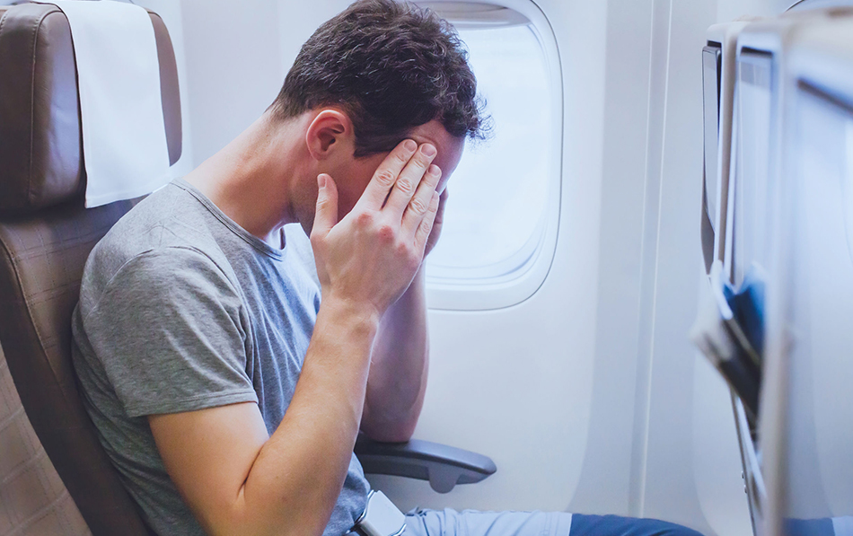 Man has head in hands due to fear of flying