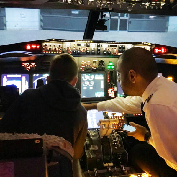 Young buy being taught by pilot instructor in 737 800 simulator